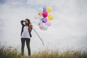 belle jeune femme hipster tenant des ballons colorés à l'extérieur photo
