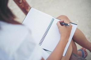 belle jeune femme sur une balançoire écrit sur son bloc-notes photo