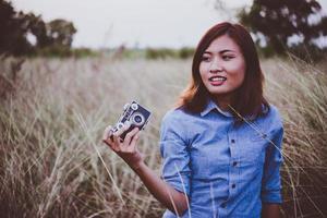 femme heureuse jeune hipster avec appareil photo vintage dans le champ