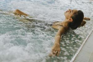 jeune femme se détendre dans le bain à remous au bord de la piscine photo