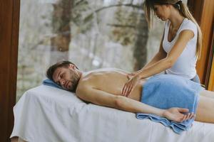 Beau jeune homme couché et ayant un massage du dos dans un salon de spa pendant la saison d'hiver