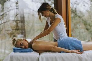 Belle jeune femme allongée et ayant un massage du cou dans un salon spa pendant la saison d'hiver