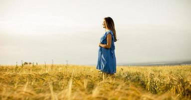 Jeune femme enceinte en robe bleue se détendre à l'extérieur dans la nature photo
