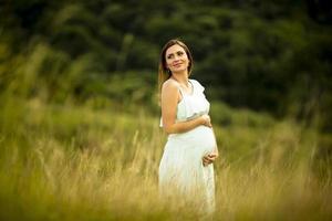 jeune femme enceinte se détendre à l'extérieur dans la nature photo