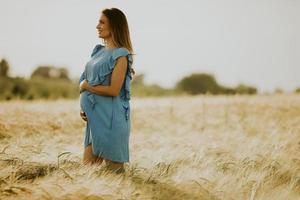 Jeune femme enceinte en robe bleue se détendre à l'extérieur dans la nature