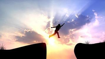 silhouette d'un homme sautant sur la falaise
