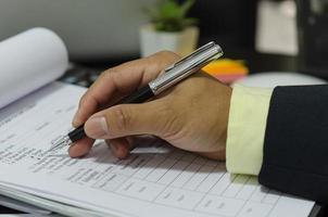 homme d & # 39; affaires tenant un stylo sur des documents commerciaux