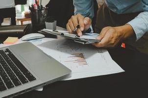 un homme d'affaires regardant des documents sur son bureau tout en tenant un stylo à la main photo