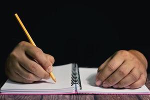 deux mains avec un crayon jaune écrit sur un ordinateur portable