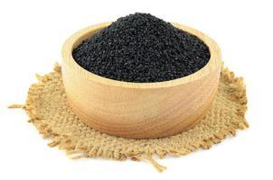 Sésame noir dans un bol en bois sur toile de jute sur fond blanc photo