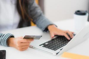 femme utilisant une carte de crédit avec un ordinateur portable pour les achats en ligne photo