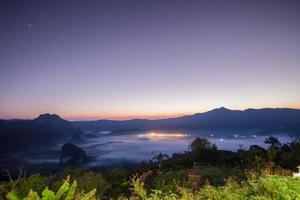 brouillard sur la ville et les montagnes au lever du soleil
