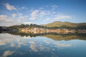 village sur une montagne reflétée dans l'eau