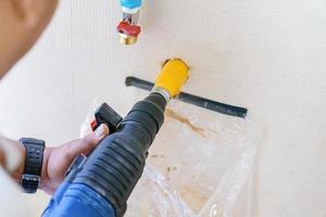 Travailleur à l'aide d'un outil électrique de forage sur chantier