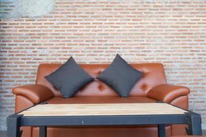 Canapé en cuir avec un fond de mur de brique marron photo
