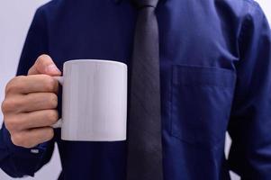 un homme tenant une tasse de café photo