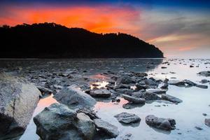 coucher de soleil rouge sur un rivage rocheux