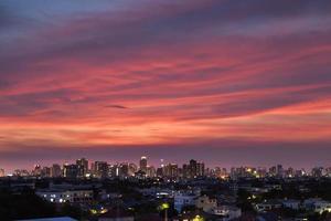 nuages roses au-dessus d'une ville au coucher du soleil