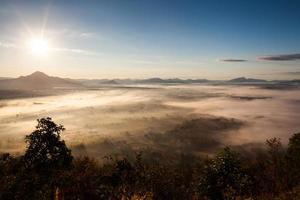 lever du soleil au-dessus d'un paysage de montagne brumeux