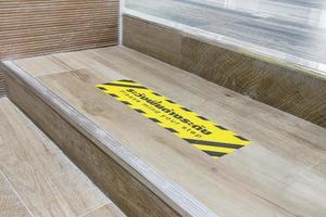 escalier avec avertissement s'il vous plaît faites attention à votre étape avec la description thaïlandaise