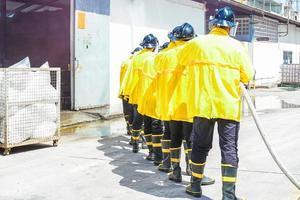 pompiers utilisant un extincteur et de l'eau photo