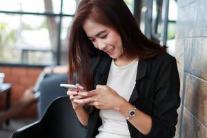 femme asiatique, jouer, sur, téléphone intelligent photo