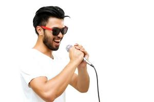 Homme asiatique avec une moustache chantant dans le microphone sur fond blanc
