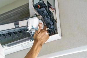 un technicien de service nettoie le climatiseur