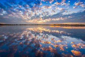 nuages coucher du soleil reflétée dans l'eau photo