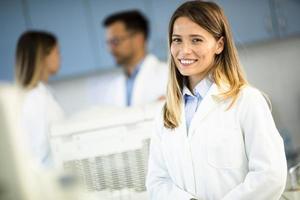 Femme scientifique en blouse blanche debout dans le laboratoire biomédical photo