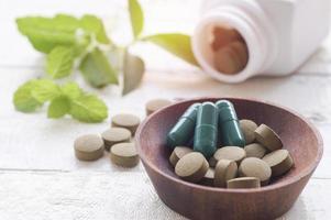 pilules à base de plantes dans un bol en bois photo