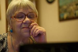 Femme senior réfléchie, lisant un écran d'ordinateur