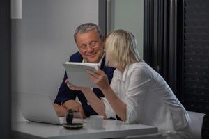 un couple d'âge moyen à table avec une tablette photo