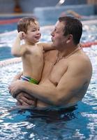 grand-père jouant avec son petit-fils dans une piscine photo