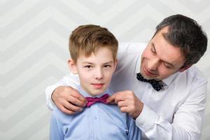 père ajustant le nœud papillon de son fils photo