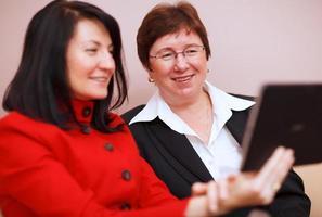 deux femmes regardant une tablette photo