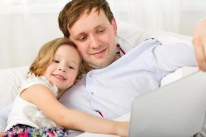 heureux papa et fille avec ordinateur portable photo