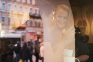couple avec caméra derrière une vitre
