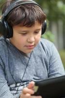 adolescent dans des écouteurs à l'aide d'une tablette photo