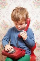 petit garçon parlant sur un téléphone rouge photo