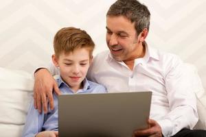 garçon et père utilisant un ordinateur portable ensemble photo