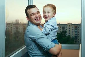 père et fils souriant sur un balcon photo