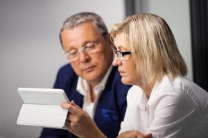 hommes d'affaires matures travaillant avec une tablette
