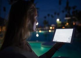 femme, utilisation, a, tablette, soir, près, a, piscine photo
