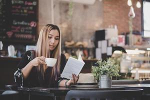 Happy business woman reading book tout en vous relaxant au café photo