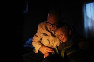grand-père embrasse son petit-fils près de la cheminée photo