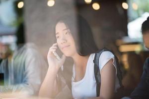 Jeune femme à l'aide de smartphone dans la fenêtre d'un café photo
