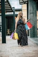 Portrait d'une jeune femme heureuse avec des sacs à provisions marchant dans la rue