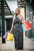 Portrait d'une jeune femme heureuse avec des sacs à provisions marchant dans la rue photo