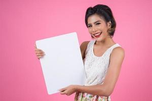 Portrait d'une femme à la mode affichant une bannière blanche photo
